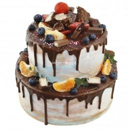 Торт праздничный в два яруса политый темным шоколадом и украшенный конфетами, ягодами, мандарином