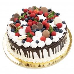 Торт праздничный белый, политый темным шоколадом, и украшенный ягодами